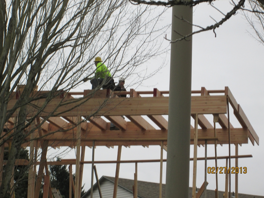 Two employees working on a second-story roof standing on trusses without fall protection.